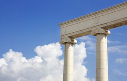 Antique columns against the blue sky and picturesque clouds royalty free stock images