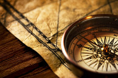 Antique compass. A closeup view of an antique compass kept on an old paper on wooden surface royalty free stock images