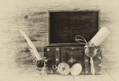 Antique compass, inkwell and old wooden chest on wooden table. black and white style old photo Stock Image