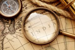 Antique compass, magnifier spyglass on map stock photography