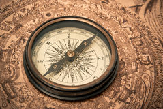Antique Compass on Map. Antique compass lying on old style map. Sepia toned Stock Photos