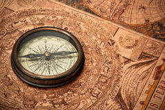 Antique Compass on Map. Antique compass lying on old style map. Sepia toned Royalty Free Stock Photography
