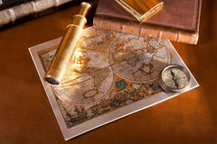 Antique compass  and old map. An antique compass and spyglass sitting on an old map Stock Photos