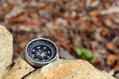 Antique compass on rock. An antique compass with the needle pointing North resting on a rock Stock Images