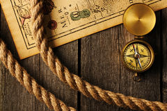 Antique compass and rope over old map. Antique brass compass and rope over old map stock photo