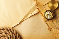 Antique compass and rope over old map. Antique brass compass and rope over old map royalty free stock photos