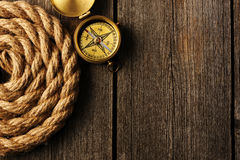 Antique compass and rope over wooden background Royalty Free Stock Image