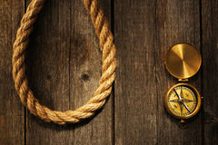 Antique compass and rope over wooden background Stock Photography