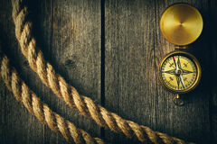Antique compass and rope over wooden background Royalty Free Stock Images