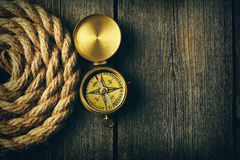 Antique compass and rope over wooden background Stock Photos