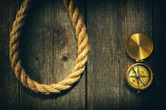 Antique compass and rope over wooden background Royalty Free Stock Photos