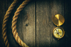 Antique compass and rope over wooden background Royalty Free Stock Photo