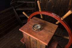 Antique Compass and Steering Wheel on Ship Deck. High Angle View of Helm of Antique Wooden Ship with Compass and Steering Wheel on Deck royalty free stock photos