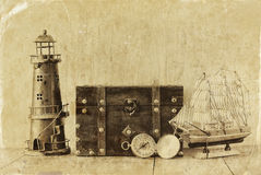 Antique compass, vintage lighthouse, wooden boat and old chest on wooden table. black and white style old photo Stock Image