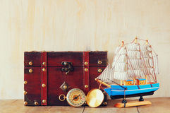 Antique compass, wooden boat and old chest on wooden table Royalty Free Stock Photos