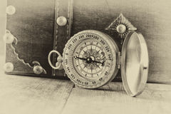 Antique compass on wooden table. black and white style old photo.  stock photos