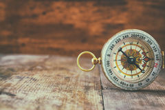 Antique compass on wooden table. retro filtered image Royalty Free Stock Image