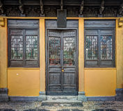The antique concrete building with carved wooden door, windows and roof Royalty Free Stock Photography