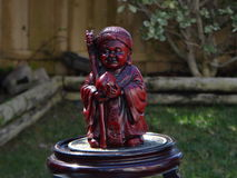 Antique Confucius figure cinnabar. Cinebarre statuette standing on 9 dragons coin royalty free stock photos
