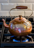 Antique copper kettle on gas stove burner. Stock Images