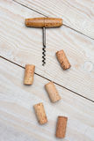 Antique Cork Screw and Corks. Closeup of an antique cork screw and five used corks on a rustic whitewashed wood table. Vertical format from a high angle Royalty Free Stock Photography