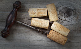 Antique corkscrew with used corks on aged wood Royalty Free Stock Images