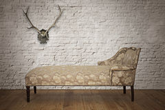 Antique couch. From Victorian era with horns on the wall Stock Photography