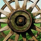 Antique country wagon wheel. Partial view of an old rusty wagon wheel, with grass and sky backgrounds Royalty Free Stock Photo