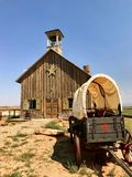 Antique covered wagon and settler church in watercolor Stock Photo
