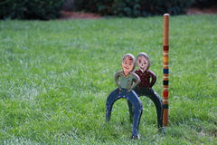 Antique croquet pieces. Vintage croquet wickets. Wickets are boys in jeans and shirts Stock Photos
