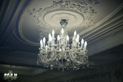 Antique crystal chandelier. Beautiful antique crystal chandelier hangs from the ceiling in the shadows Stock Image