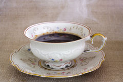 Antique cup with hot coffee. Antique cup with hot steaming coffee on the sackcloth Stock Photos