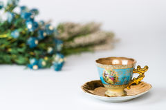 Antique cup and saucer. Decorated in gold and blue with blurry background of French flowers Royalty Free Stock Photography