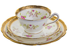Antique cup, saucer and small plate. Dainty tea cup, saucer and small plate isolated on white Royalty Free Stock Photography