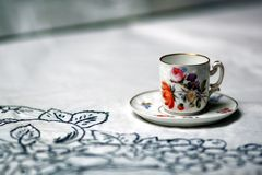 Antique cup on table. Hand painted espresso cup on a white tablecloth Royalty Free Stock Images
