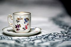 Antique cup on table. Hand painted espresso cup on a white tablecloth Stock Photo