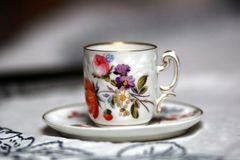 Antique cup on table. Hand painted espresso cup on a white tablecloth Royalty Free Stock Photo