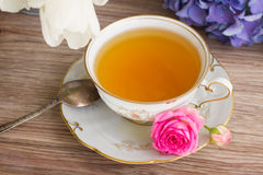 Antique cup of tea with flowers Stock Photo