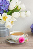 Antique cup of tea with tulips Royalty Free Stock Photo