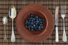 Antique cutlery and jarrah bowl filled with berries Royalty Free Stock Image