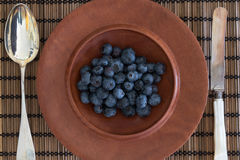 Antique cutlery and jarrah bowl filled with berries Royalty Free Stock Images