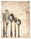 Antique cutlery and old cook book page. Retro kitchen utensils knife, fork and spoons royalty free stock photography