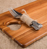 Antique cutlery wrapped in hessian on acacia wood chopping board Stock Photos