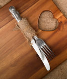 Antique cutlery wrapped in hessian on acacia wood chopping board Royalty Free Stock Image