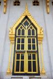 Or antique découpant la porte en bois du temple thaïlandais Photo stock
