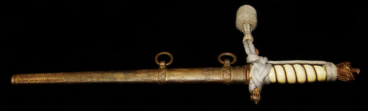 Antique dagger. Side view of antique or vintage dagger in scabbard; isolated on black background Royalty Free Stock Photo