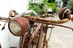 Antique and damaged bicycle parked next to wall Stock Photography
