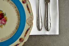 Antique decorative flowered dinner plate,napkin and vintage silverware.  stock photography