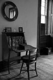 Antique desk and chair. An old antique folding desk and chair with many empty bottles in an old fashioned room.  Black and white image Stock Image