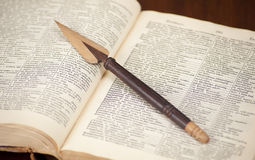 Antique dictionary with wooden knife on it Royalty Free Stock Photos